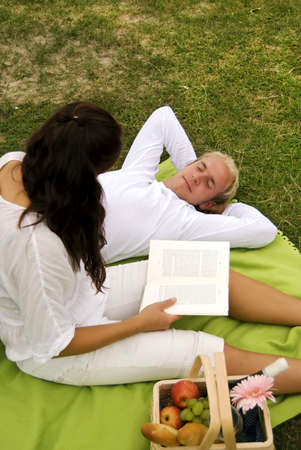 A young woman reads poetry to her handsome partner during a romantic picnic photo