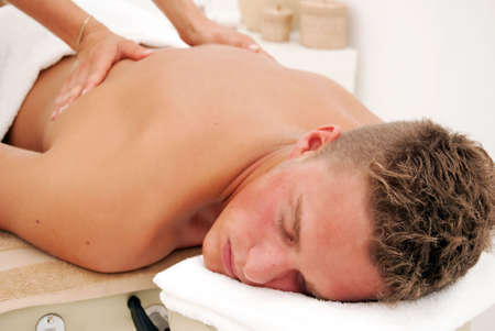 massaging: A young man relaxes as he enjoys a luxurious spa treatment from a female masseuse. Stock Photo