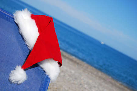 A santa hat resting on a sun lounger by an exotic beach to give a christmas vacation concept. photo