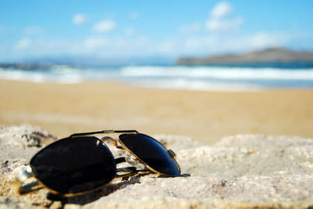 A pair of trendy sunglasses lying on an exotic beach location. Stock Photo - 5732149
