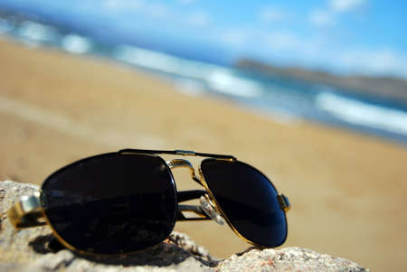 A pair of trendy sunglasses lying on an exotic beach location. Stock Photo - 5767469