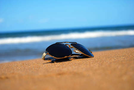 A pair of trendy sunglasses lying on an exotic beach location. Stock Photo - 5767467