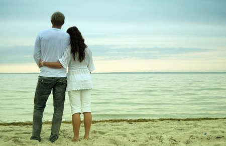 mujeres de espalda: Una mujer bella y joven tiene a su pareja hermosa como miran la puesta de sol junto a una playa rom�ntica.
