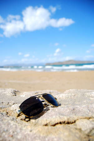 A pair of trendy sunglasses lying on an exotic beach location. Stock Photo - 5787056
