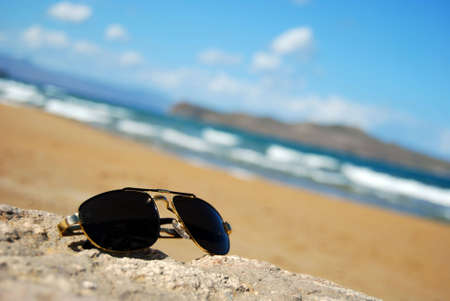 A pair of trendy sunglasses lying on an exotic beach location. Stock Photo - 5888719