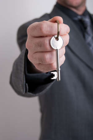 A real estate agent holds out the front door key of a new home to a lucky buyer. Stock Photo - 5959492