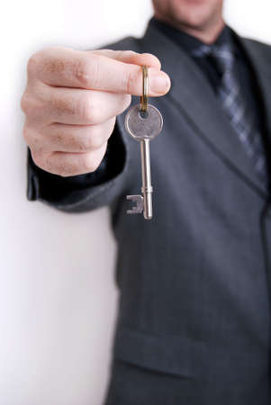 A real estate agent holds out the front door key of a new home to a lucky buyer. photo