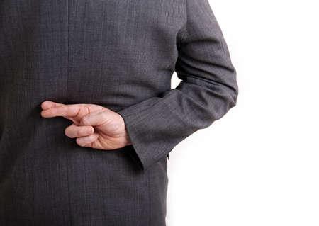 mani incrociate: Un'immagine conceptial di un uomo d'affari con le dita incrociate dietro la schiena.