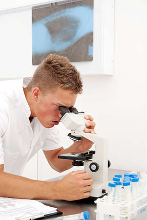 earlier: A young male lab technician looks at slides through a microscope whilst comparing the results to earlier tests. Stock Photo