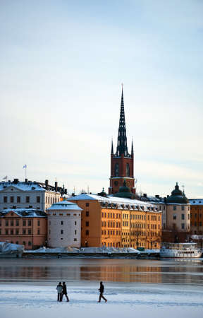 locals: A view of Stockholms gamla stan region with locals walking across the frozen river in winter time. Stock Photo