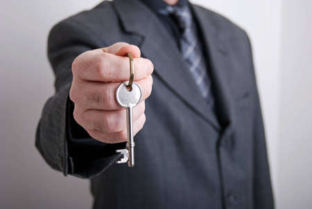 A real estate agent holds out the front door key of a new home to a lucky buyer. Stock Photo - 6726968