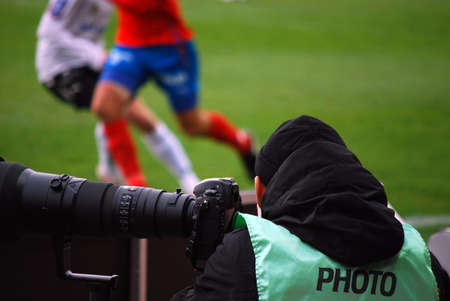 A sports photographer watches and shoots the action at a football match. Stock Photo