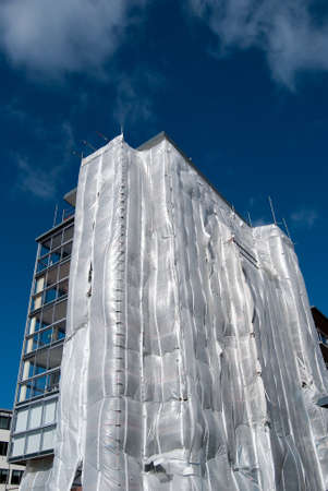 A block of flats covered in plastic sheets and scaffolding in the process of getting renovated photo