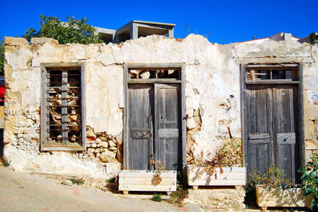 crumbling: A view of an old crumbling building in the greek town of Platanius. Stock Photo