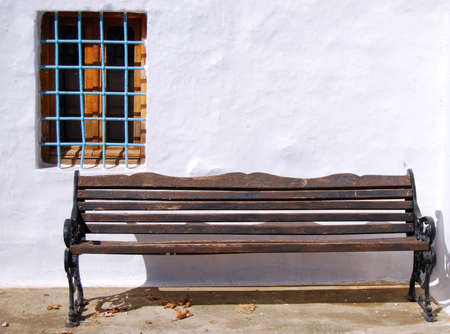 white washed: An old weathered wooden bench against a white washed wall on the Greek island of Crete. Stock Photo
