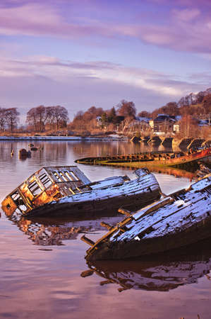 Sunken fishing boats lined up in the scottish harbour at Bowling. photo