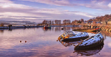 A panoramic image of sunken fishing boats lined up in the scottish harbour at Bowling. photo