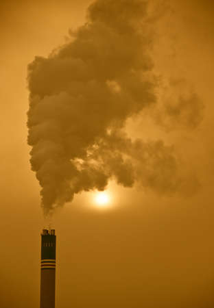 An industrial image of a factory chimney spewing waste into the atmosphere photo