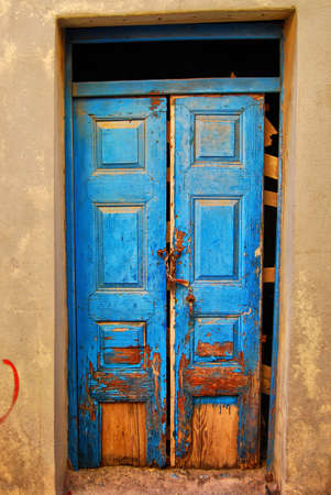 A very worn and battered old blue door locked with a rusty chain situated on the Greek isle of Crete. photo