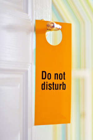 A hotel doorknob label with the words Do not disturb on it. photo
