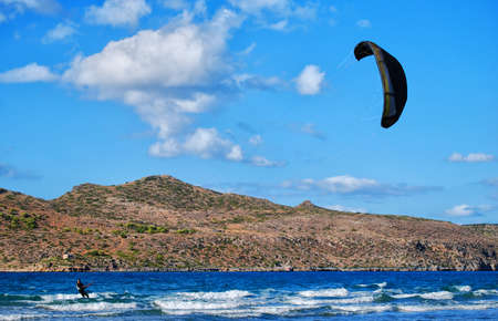 A kitesurfer has the time of his life riding the ocean waves on a sail full of wind photo