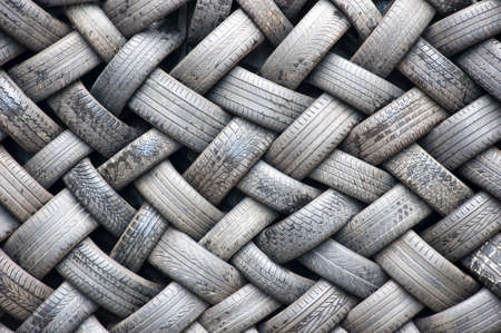 A background abstract image of a wall made entirely of rubber tyres. photo