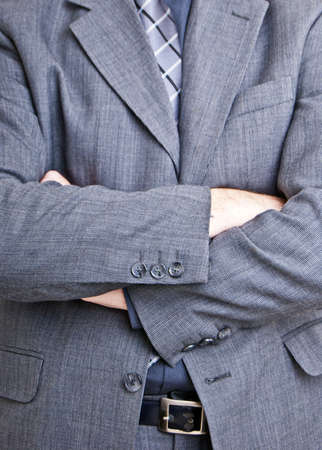A close up shot of a business man standing with folded arms filling the entire frame of the photo. photo