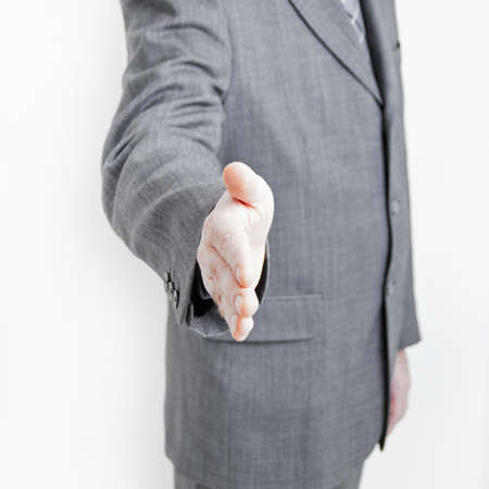 A business man makes a hand shake gesture in your direction. Stock Photo - 9754618