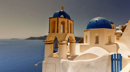 A sunset view of a couple of the famous blue domed churches from Oia on the greek isle of Santorini.