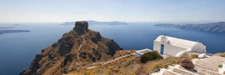 A panoramic image from Santorini of a typical greek church overlooking the rock of skaros with the town of Oia and the volcano in the background. photo