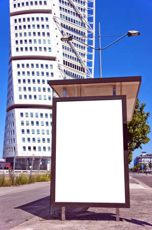 An image of a bus stop with a blank bilboard for your advertising situated in front of the turning torso skyscraper in the swedish city of Malmo. photo