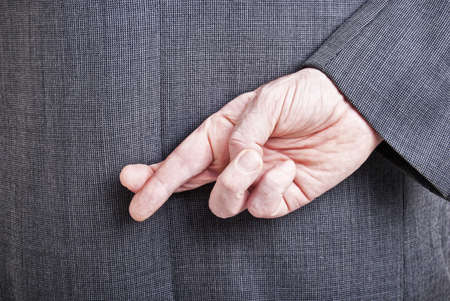 A conceptial image of a business man with his fingers crossed behind his back. Stock Photo