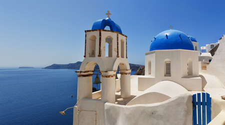 A panoramic view of a couple of the famous blue domed churches from Oia on the greek isle of Santorini. photo