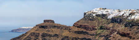 A panoramic image from Santorini of the villages of imerovigli and Oia with the rock of skaros in between them. photo