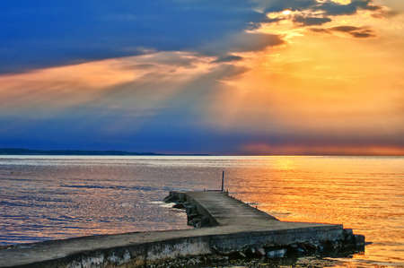 A spectacular sunset at Torekov in Sweden with a deserted pier in the foreground. Stock Photo - 10200688