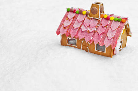 A cute and tasty looking gingerbread house on top of some snow. Stock Photo