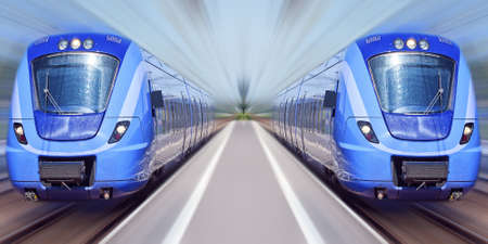 Two passenger trains travel at high speed through a train station with everything bar the trains blurred out.
