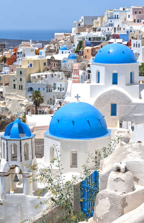 A view of a few of the famous blue domed churches from Oia on the greek isle of Santorini. photo