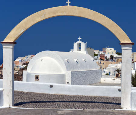 A view of a famous white church from Oia on the greek isle of Santorini. photo