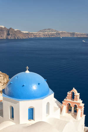 A view of a famous blue domed church from Oia on the greek isle of Santorini. photo