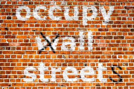 occupy wall street: An image of a political message painted on a brick wall in an urban location Stock Photo