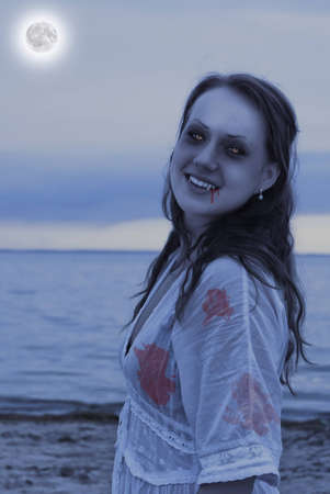 A beautiful young vampire woman on the beach at twilight looks at you and smiles. photo