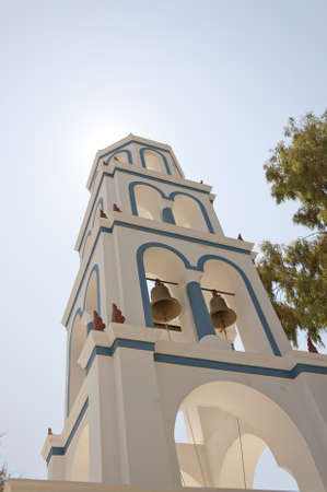 One of the many bell towers that adorn the churches on the greek island of santorini. photo