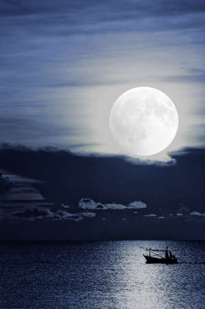 A fishing boat off Thailand returns home under moonlight after setting be its nets and baskets for the night.