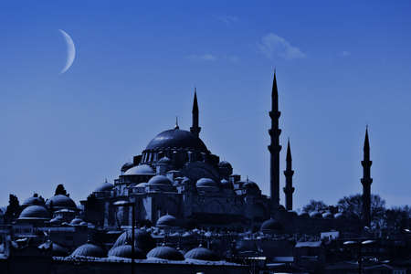 A night view of the majestic Suleiman Mosque in Istanbul with crescent moon in the sky. photo
