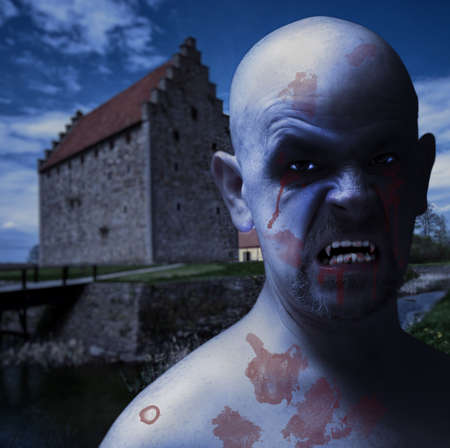 An evil looking vampire male with a spooky castle backdrop. photo