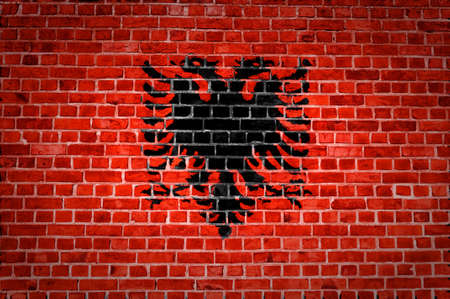 An image of the Albanian flag painted on a brick wall in an urban location photo