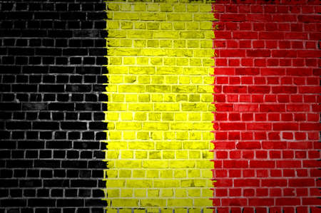 belgium flag: An image of the Belgium flag painted on a brick wall in an urban location
