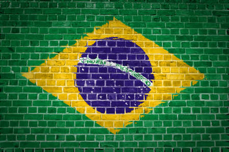 An image of the Brazil flag painted on a brick wall in an urban location