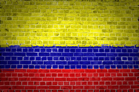 An image of the Colombia flag painted on a brick wall in an urban location photo